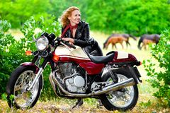 Biker girl in leather jacket on a motorcycle Royalty Free Stock Image