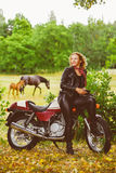 Biker girl in leather jacket on a motorcycle royalty free stock photos