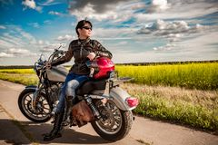 Biker girl on a motorcycle. Biker girl in a leather jacket on a motorcycle Stock Photos