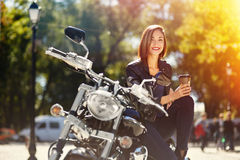 Biker girl in a leather jacket on a motorcycle drinking coffee Stock Images