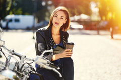 Biker girl in a leather jacket on a motorcycle drinking coffee Royalty Free Stock Images