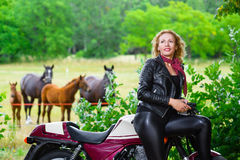 Biker girl in leather jacket on a motorcycle over Royalty Free Stock Photography