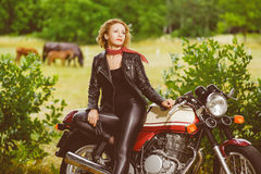 Biker girl in leather jacket on a motorcycle over Stock Image