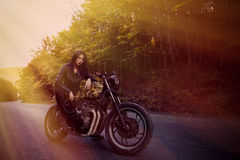 Biker girl in a leather jacket on a motorcycle Stock Image