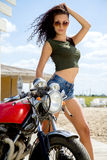 Biker girl in a leather jacket on a motorcycle. Biker young adult attractive brunette girl on a motorcycle Stock Image