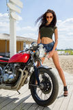Biker girl in a leather jacket on a motorcycle Royalty Free Stock Photography