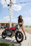 Biker girl in a leather jacket on a motorcycle Royalty Free Stock Photos