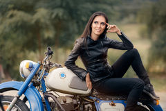 Biker Girl in Leather Jacket on Retro Motorcycle stock image