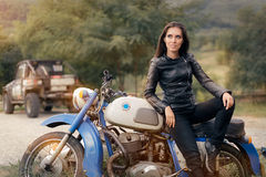 Biker Girl in Leather Jacket on Retro Motorcycle stock images