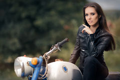 Biker Girl in Leather Jacket on Retro Motorcycle royalty free stock photos