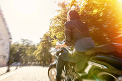 Biker girl in a leather jacket riding a motorcycle Stock Image