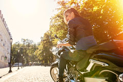 Biker girl in a leather jacket riding a motorcycle Stock Images