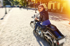Biker girl in a leather jacket riding a motorcycle Royalty Free Stock Photos