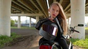 Biker girl with moto helmet sitting on motorcycle under car bridge in city. Moto girl in black leather jacket posing on. Motorbike on urban landscape stock footage