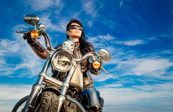 Biker girl on a motorcycle. Biker girl in a leather jacket on a motorcycle Stock Image