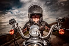 Biker girl on a motorcycle. Biker girl in a leather jacket and helmet on a motorcycle Stock Image