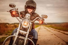 Biker girl on a motorcycle. Biker girl in a leather jacket and helmet on a motorcycle Stock Images