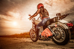 Biker girl on a motorcycle. Biker girl in a leather jacket and helmet on a motorcycle
