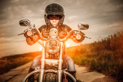 Biker girl on a motorcycle. Biker girl in a leather jacket and helmet on a motorcycle Stock Photos