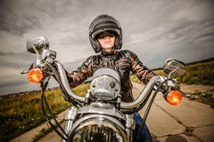 Biker girl on a motorcycle. Biker girl in a leather jacket and helmet on a motorcycle Stock Photography