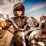 Biker girl on a motorcycle. Biker girl in a leather jacket and helmet on a motorcycle Royalty Free Stock Images