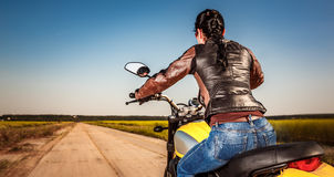 Biker girl on a motorcycle. Biker girl in a leather jacket and helmet on a motorcycle Royalty Free Stock Photography