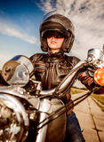 Biker girl on a motorcycle. Biker girl in a leather jacket and helmet on a motorcycle Royalty Free Stock Photo