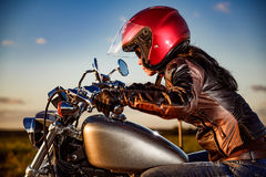 Biker girl on a motorcycle. Biker girl in a leather jacket and helmet on a motorcycle Royalty Free Stock Photos