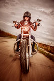 Biker girl on a motorcycle. Biker girl in a leather jacket and helmet on a motorcycle Royalty Free Stock Image