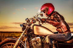 Biker girl on a motorcycle. Biker girl in a leather jacket and helmet on a motorcycle Stock Photo