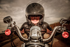 Biker girl on a motorcycle. Biker girl in a leather jacket and helmet on a motorcycle. Filter applied in post-production Royalty Free Stock Photos