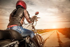 Biker girl on a motorcycle. Biker girl in a leather jacket and helmet on a motorcycle. Focus on the fuel tank Stock Images