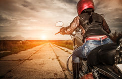 Biker girl on a motorcycle. Biker girl in a leather jacket and helmet on a motorcycle. Focus on the fuel tank Royalty Free Stock Photo