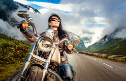 Biker girl on a motorcycle. Biker girl in a leather jacket on a motorcycle looking at the sunset Royalty Free Stock Image