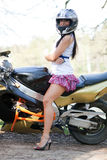 Biker Girl On A Motorcycle. Biker Girl standing beside a motorcycle. beautiful woman standing next to a motorcycle Outdoors. girl in a short skirt and sportbike Royalty Free Stock Photography