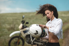 Biker girl next to a motorcycle Royalty Free Stock Photography