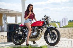 Biker Girl on Retro Motorcycle royalty free stock images
