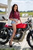 Biker Girl on Retro Motorcycle. Portrait of a cool woman on a vintage motorbike Royalty Free Stock Photo