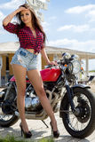 Biker Girl on Retro Motorcycle. Portrait of a cool woman on a vintage motorbike Royalty Free Stock Photography