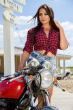 Biker Girl on Retro Motorcycle. Portrait of a cool woman on a vintage motorbike Royalty Free Stock Image
