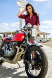 Biker Girl on Retro Motorcycle. Portrait of a cool woman on a vintage motorbike Stock Images