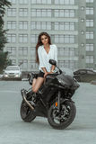 Biker girl rides a motorcycle in the rain. First-person view Royalty Free Stock Image