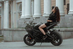 Biker girl rides a motorcycle in the rain. First-person view Stock Image