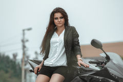 Biker girl rides a motorcycle in the rain. First-person view.  Stock Image