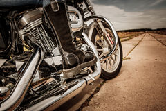 Biker girl riding on a motorcycle. Bottom view of the legs in leather boots Stock Photography