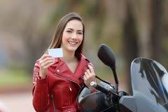 Biker girl showing a blank credit card stock photo
