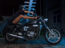 Biker girl sits on a chopper motorcycle Stock Image
