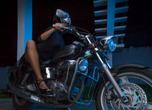 Biker girl sits on a chopper motorcycle Royalty Free Stock Image