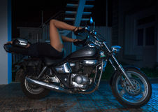 Biker girl sits on a chopper motorcycle Stock Photos