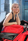 Biker girl sitting on her bike on urban background Royalty Free Stock Photos